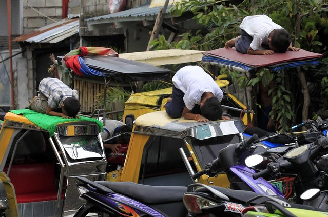 Muslim youths pray atop motorcycle taxis during the fasting month of Ramadan in front of Al-Satie Mosque in Baseco, Tondo city, metro Manila July 4, 2014. (Photo by Romeo Ranoco/Reuters)