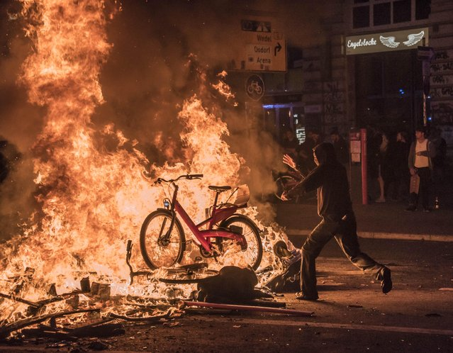 A protester is throwing public city bikes into the burning barricade in Hamburg, Germany on July 7, 2017. Violent demonstrations against the Group of 20 summit meeting led to clashes between the police and protesters on the second consecutive night. (Photo by Daniel Dohlus/ZUMA Wire/Rex Features/Shutterstock)