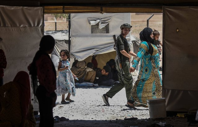 A female fighter from the Kurdish Women's Protection Units (YPJ) walks between displaced Syrians who fled the countryside surrounding the Islamic State (IS) group's Syrian stronghold of Raqa, at a temporary camp in the village of Ain Issa on July 11, 2017. (Photo by Bulent Kilic/AFP Photo)