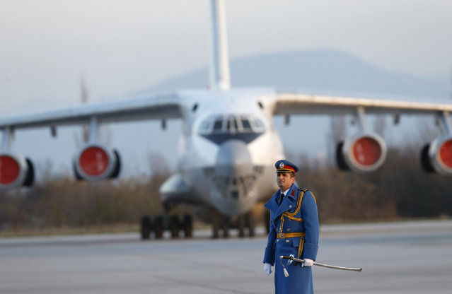 """In this photo taken Sunday, November 20, 2016, a Serbian army officer walks in front of Soviet made heavy cargo plane Ilyushin Il-76 on the tarmac at the Constantine the Great Airport, near a """"Russian-Serbian Humanitarian Center"""" in the town of Nis, Serbia. The U.S. embassy in Belgrade says in a statement obtained Saturday, July 15, 2017 by The Associated Press, there is no need to grant a diplomatic status to the Russian staff of a controversial facility in Serbia that some consider a spy base but Moscow insists is a disaster relief center. (Photo by Darko Vojinovic/AP Photo)"""