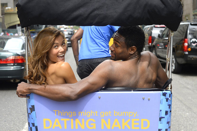 """Kelly Keodara and Yarc Lewinson ride around Grand Central Station in New York on July 16, 2014 in a pedicab to promote a new VH1 series to the roster called """"Dating Naked"""", which is built on the premise of stripping away the outer trappings of attraction by dating naked. The series,is filmed on a remote exotic locale, and each closed-ended episode will feature a man and a woman as they each date two different, naked suitors. (Photo by Timothy A. Clary/AFP Photo)"""