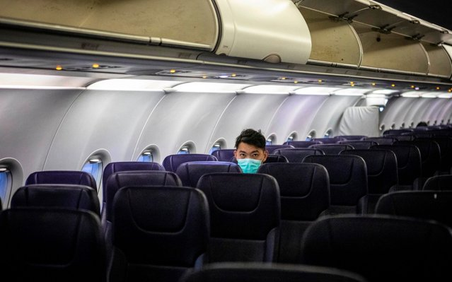 A passengers sits in a mostly empty airplane wearing protection mask against the coronavirus during the flight bound from Sihanoukville, Cambodia via Phnom Penh, Cambodia to Guangzhou, Guangdong Province, China, 01 February 2020. Guangzhou Airport, usually busy during the end of Spring Festival when Chinese travelers return to their homes, appeared deserted after many countries and international airlines suspended or limited flights to and from China, because of outbreak of coronavirus in Wuhan City. (Photo by Alex Plavevski/EPA/EFE/Rex Features/Shutterstock)