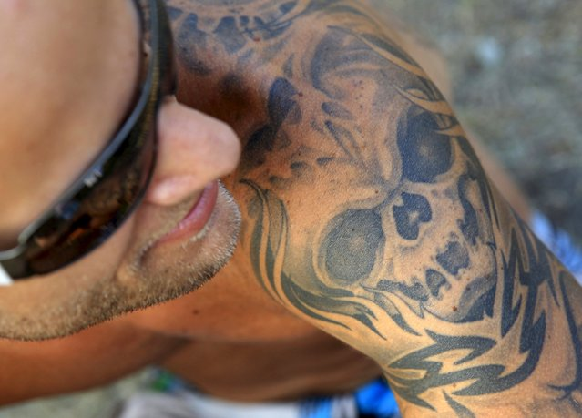 Peter Prechtl, 27, from Germany shows his tattoo during the Sziget music festival on an island in the Danube River in Budapest, Hungary, August 14, 2015. (Photo by Bernadett Szabo/Reuters)