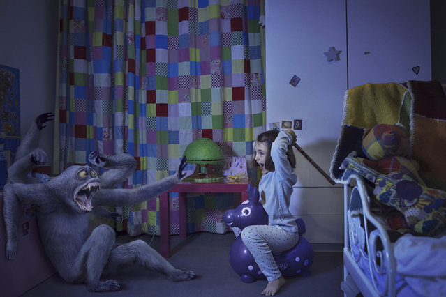 """Sixtine fights a monster in her bedroom in Laure Fauvel's """"Terreurs"""", 2014, in Paris, France. An imaginative photographer has brought to life monsters that haunt children's nightmares. Armed with sticks, wands and swords the eight and nine year-olds appear to be getting the upper-hand against the villains. Parisian photographer Laure Fauvel, 22, said: I wanted the children not be victims and to fight the monsters. (Photo by Laure Fauvel/Barcroft Media)"""