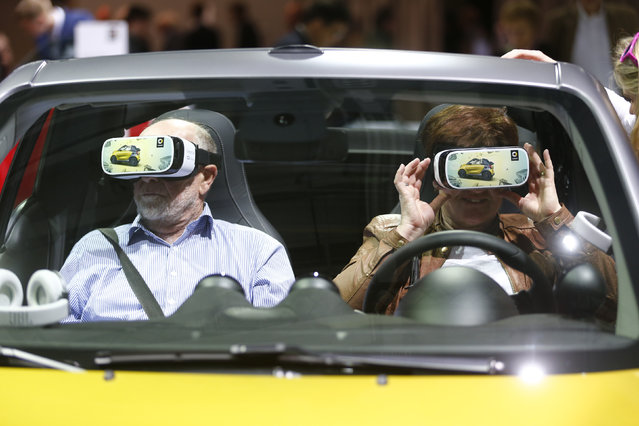 """People use virtual reality goggles while sitting in a """"smart fortwo cabrio"""" car prior to the Daimler annual shareholder meeting in Berlin, Germany, April 6, 2016. (Photo by Hannibal Hanschke/Reuters)"""