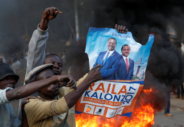 A supporter of opposition leader Raila Odinga holds his poster in front of a burning barricade in Kibera slum in Nairobi, Kenya, August 9, 2017. (Photo by Goran Tomasevic/Reuters)