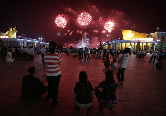 North Koreans watch as fireworks explode, Sunday, July 27, 2014 in central Pyongyang, North Korea. North Koreans gathered at Kim Il Sung Square to watch a fireworks display as part of celebrations for the 61st anniversary of the armistice that ended the Korean War. (Photo by Wong Maye-E/AP Photo)