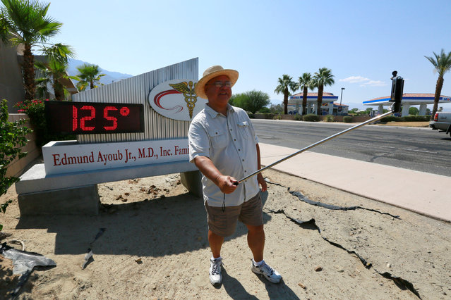 Palm Springs resident Benito Almojuela takes a selfie near a thermometer sign which reads 125 degrees in Palm Springs, California, U.S. June 20, 2016. (Photo by Sam Mircovich/Reuters)