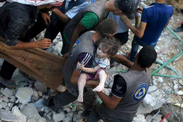 A medic carries an injured girl that survived from under debris caused by what activists said was barrel bombs dropped by forces loyal to Syria's President Bashar Al-Assad in Douma, Eastern Al-Ghouta, near Damascus, Syria August 22, 2015. (Photo by Bassam Khabieh/Reuters)