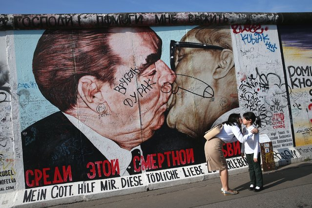 A woman kisses a child in a manner similar a mural to former Soviet leader Leonid Brezhnev kissing former East German communist leader Erich Honecker on a mural by Russian painter Dmitri Vrubel on the former Berlin Wall at the East Side Gallery on August 5, 2014 in Berlin, Germany. The East Side Gallery is a surviving portion of the Wall known for its murals and is one of the citys main tourist attractions. (Photo by Sean Gallup/Getty Images)