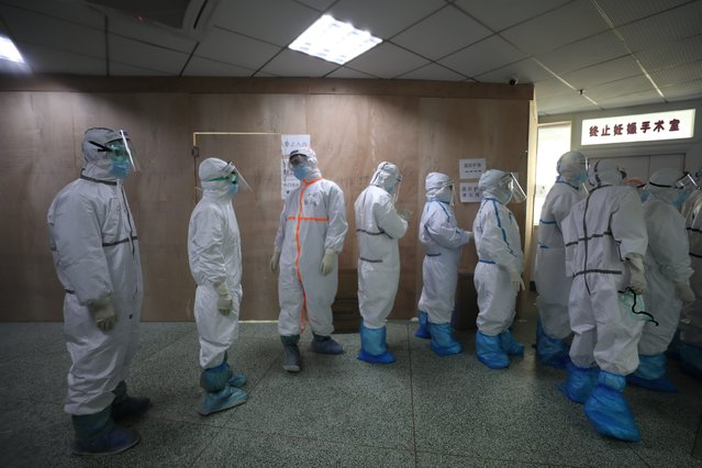 Medical staff in isolation gowns prepare to enter the isolation zone in a hospital designated for COVID-19 patients in Wuhan in central China's Hubei province Tuesday, February 25, 2020. Doctors and nurses of other disciplines in the hospital were all assigned to respiratory patients upon the official announcement of the outbreak, and 51 of them contracted SARS-COV-2 during that time due to lack of protection. Their first reinforcement of 138 medical personnel came to rescue on Jan. 26. (Photo by Feature China/Barcroft Media via Getty Images)