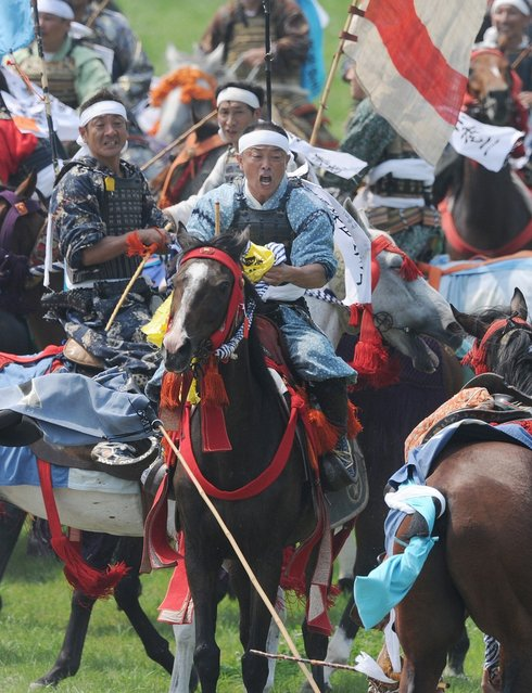 """A local man in samurai armor riding his horse reacts after catching a yellow sacred flag at the annual Soma Nomaoi Festival in Minamisoma, Fukushima Prefecture, on July 29, 2012. Some 400 horses and thousands of people took part in the 1,000-year-old """"Soma Nomaoi"""", or wild horse chase, at the weekend in the shadow of Japan's crippled Fukushima nuclear plant. (Photo by Toru Yamanaka/AFP Photo)"""