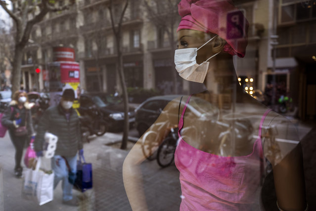People wearing masks and carrying supplies walk past a mannequin wearing a mask in downtown Barcelona, Spain, Saturday, March 14, 2020. Spain's prime minister has announced a two-week state of emergency from Saturday in a bid to contain the new coronavirus outbreak. For most people, the new coronavirus causes only mild or moderate symptoms. For some, it can cause more severe illness, especially in older adults and people with existing health problems. (Photo by Emilio Morenatti/AP Photo)