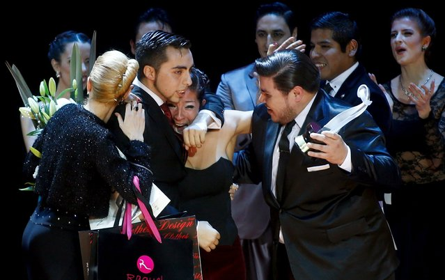 Jonathan Saavedra (2nd L) and Clarisa Aragon from Argentina, who are representing the Argentine city of Cordoba, embrace after winning the Tango World Championship in Salon style as other couples cheer, in Buenos Aires August 26, 2015. (Photo by Marcos Brindicci/Reuters)