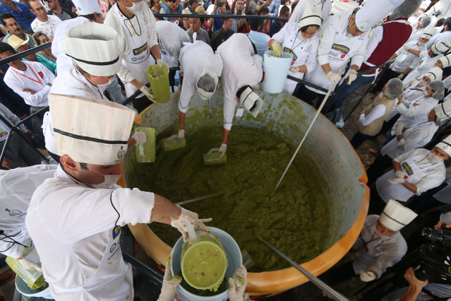Volunteers from a culinary school mix mashed avocados as they attempt to set a new Guinness World Record for the largest serving of guacamole in Concepcion de Buenos Aires, Jalisco, Mexico September 3, 2017. (Photo by Fernando Carranza/Reuters)