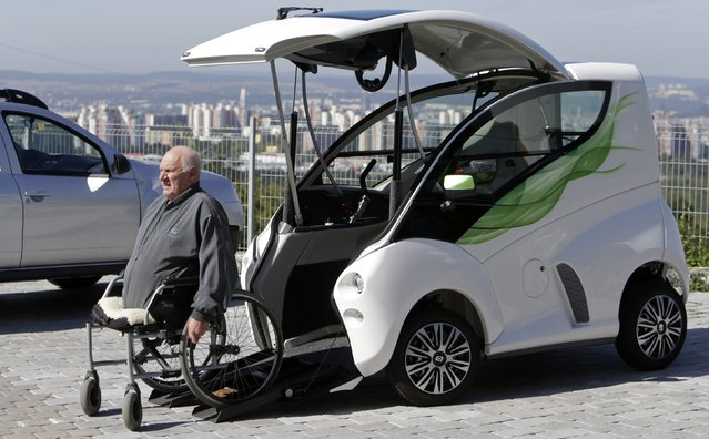 Frantisek Trunda, 67, who lost his legs in 2006, moves himself into his Elbee vehicle while seated on a wheelchair in Brno August 18, 2014. The Elbee is a vehicle designed specifically for wheelchair-bound people, and allows them to drive the vehicle without needing to get off their wheelchair or receive assistance from another person. (Photo by David W. Cerny/Reuters)