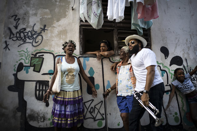 A member of the The Soul Rebels Band poses for a photo with several woman during the music conga through the streets of Old Havana within the activities of the 35th Havana Jazz Plaza festival in Havana, Cuba, Wednesday, January 15, 2020. (Photo by Ramon Espinosa/AP Photo)
