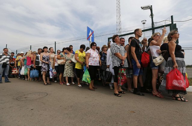 People stand in a line to cross the border and walk onto the territory of Ukraine at Russia-Ukraine border crossing point «Donetsk» in Russia's Rostov Region, August 22, 2014. (Photo by Alexander Demianchuk/Reuters)