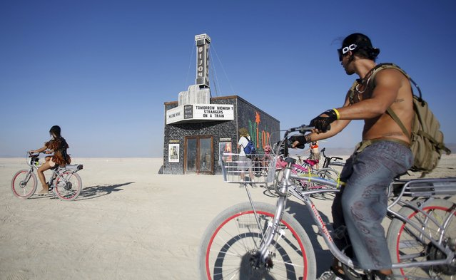 """People ride past the Black Rock Bijou, a movie theater far out on the Playa during the Burning Man 2015 """"Carnival of Mirrors"""" arts and music festival in the Black Rock Desert of Nevada, August 31, 2015. (Photo by Jim Urquhart/Reuters)"""