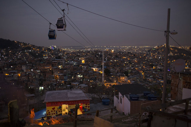 In this July 19, 2016 photo, cable cars transport commuters over the Complexo do Alemao, a sprawling cluster of slums in north Rio de Janeiro, Brazil. Just a short drive from upscale Rio districts like Ipanema and Copacabana, steep and narrow entryways lead to slums where poverty and gun violence dominate daily life for hundreds of thousands of residents. (Photo by Felipe Dana/AP Photo)