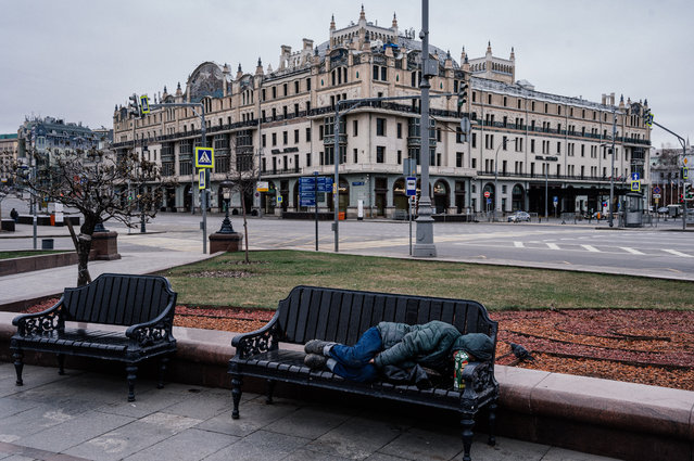 """A man sleeps on a bench on a deserted street of downtown Moscow on March 30, 2020 as the city and its surrounding regions imposed lockdowns today, that were being followed by other Russian regions in a bid to slow the spread of the COVID-19 infection caused by the novel coronavirus. The enforcement of the strict new rules, which Moscow Mayor suddenly announced for the capital late Sunday, coincide with the beginning of a """"non-working"""" week declared by Russian President the week before. (Photo by Dimitar Dilkoff/AFP Photo)"""