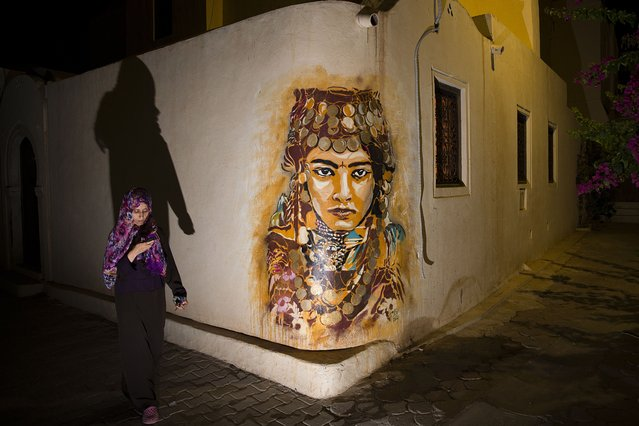 """A woman walks past a mural by Spanish artist B-TOY in the village of Erriadh, on the Tunisian island of Djerba, on August 7, 2014, as part of the artistic project """"Djerbahood"""". (Photo by Joel Saget/AFP Photo)"""