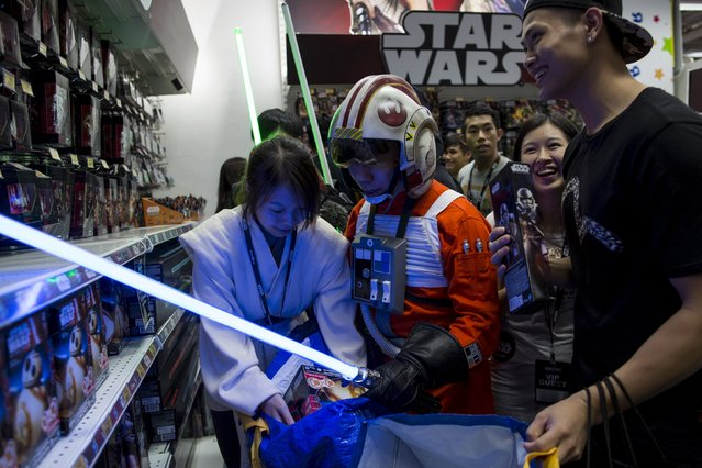 """A fan (C) dressed as Luke Skywalker picks new toys from the upcoming film """"Star Wars: The Force Awakens"""" on """"Force Friday"""" in Hong Kong, China, September 4, 2015. (Photo by Tyrone Siu/Reuters)"""