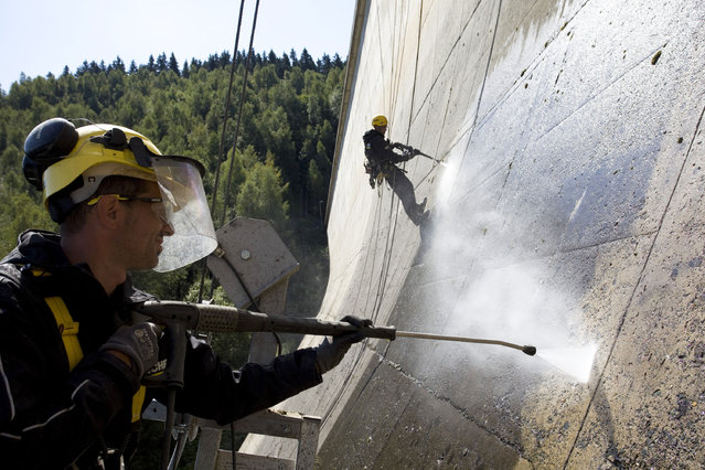 Two men clean the Eibenstock Dam in Germany. (Photo by Caters News Agency)