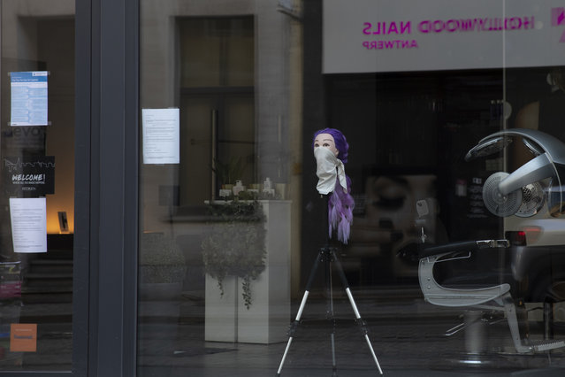 A mannequin head with a scarf around the nose and mouth is placed on a tripod in the window of a hairdressing salon in Antwerp, Belgium, Monday, March 23, 2020. After Belgian Prime Minister Sophie Wilmes announced that hairdressers would still be able to operate, while many other stores were required to be closed during the coronavirus epidemic, some thought it was a bad Belgian joke. Fearing for their health, some hairdressers now are calling on the government to order the closure of all salons without delay. (Photo by Virginia Mayo/AP Photo)