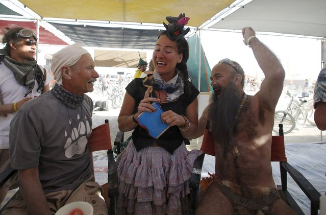 "Participants (from L) Mike Ryan, Dasha and Zoom Zoom visit over drinks at the Orphan Endorphin camp during the Burning Man 2015 ""Carnival of Mirrors"" arts and music festival in the Black Rock Desert of Nevada, September 2, 2015. Participants from all over the world attend the sold-out festival to spend a week in the remote desert to experience art, music and the unique community that develops. (Photo by Jim Urquhart/Reuters)"