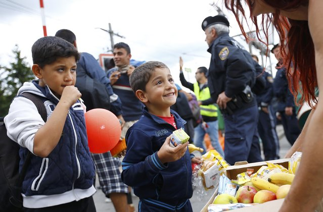 A volunteer distrubutes food to migrants at the railway station in Nickelsdorf, Austria September 6, 2015. (Photo by Leonhard Foeger/Reuters)