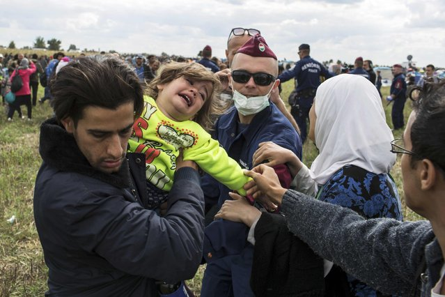 A migrant carrying a baby is stopped by a Hungarian policeman as he tries to escape a collection point in Roszke village, Hungary, September 8, 2015. (Photo by Marko Djurica/Reuters)