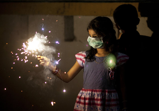 An Indian girl wears a mask while playing with firecrackers to celebrate Diwali in Hyderabad, India, Thursday, October 19, 2017. Hindus light lamps, wear new clothes, exchange sweets and gifts and pray to goddess Lakshmi during Diwali, the festival of lights. (Photo by Mahesh Kumar A./AP Photo)