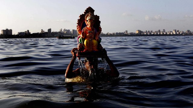 A man carries an idol of the Hindu elephant-headed god Ganesha to immerse it in the Arabian Sea on the fifth day of the ten day long Ganesh Chaturthi festival in Mumbai, India, on September 25, 2012. (Photo by Rajanish Kakade/Associated Press)