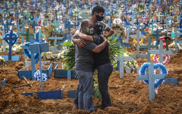 Relatives of a deceased person wearing protective masks mourn during a mass burial of coronavirus (COVID-19) pandemic victims at the Parque Taruma cemetery on May 19, 2020 in Manaus, Brazil. Brazil has over 260,000 confirmed cases and more than 17,000 deaths caused by coronavirus (COVID-19) pandemic. (Photo by Andre Coelho/Getty Images)