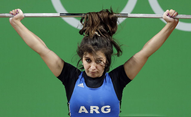 The hair of Joana Palacios, of Argentina, flips over the barbell as she competes in the women's 63kg weightlifting competition at the 2016 Summer Olympics in Rio de Janeiro, Brazil, Tuesday, August 9, 2016. (Photo by Mike Groll/AP Photo)
