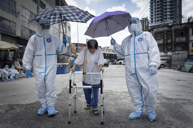 Health officials escort an elderly women back home under hot sun after she had a coronavirus test at a wet market in Kuala Lumpur, Malaysia, on Tuesday, May 5, 2020. Malaysia's government says all foreign workers must undergo mandatory virus testing as many business sectors reopen in parts of the country for the first time since a partial virus lockdown began March 18. (Photo by Vincent Thian/AP Photo)