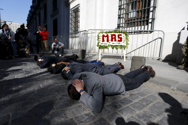 "Activists perform as the people who were detained during the coup d'etat led by former dictator Augusto Pinochet next to the ""La Moneda"" Presidential Palace during a rally in Santiago September 11, 2015. Friday marked the 42nd anniversary of the coup d'etat in Chile that ushered in a 17-year dictatorship under Pinochet. (Photo by Ivan Alvarado/Reuters)"