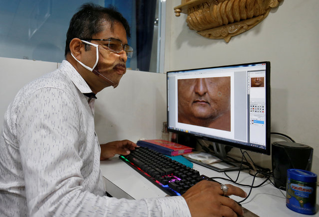 A man designs a face mask with the photograph of a customer printed on it, amid the spread of the coronavirus disease (COVID-19), at a photo studio in Gandhinagar, India, May 27, 2020. (Photo by Amit Dave/Reuters)