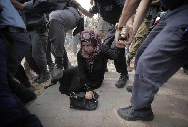 A Palestinian activist is arrested by Israeli soldiers as dozens of Palestinians block the entrance to branch of the Rami Levy supermarket opened  in Shaar Binyamin close to the city of Ramallah in the Israeli occupied Palestinian West Bank on October 24, 2012, as the protesters called for a boycott of goods being produced in the Jewish Settlement. (Photo by Ahmad Gharabli/AFP Photo)