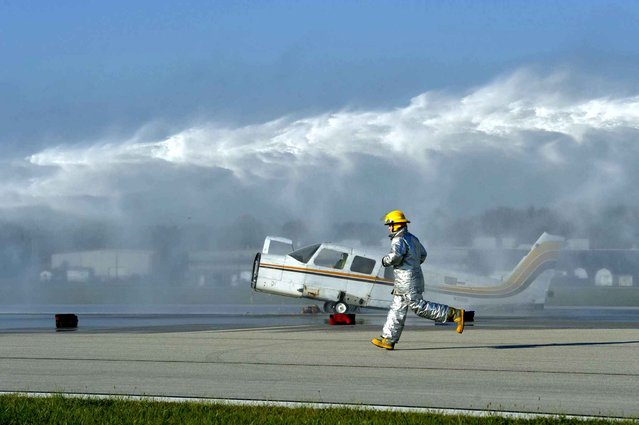 An Evansville Regional Airport Firefighter runs past a burning plane as he goes to check on a large group of victims after being the first on the scene during a mock disaster airplane crash at the Evansville Regional Airport in Evansville, Ind., Tuesday, September 30, 2014. About 25 local first responder agencies from around the Tri-State participated in the mock drill that the airport is required to perform every three years according to the Federal Aviation Administration. (Photo by Erin McCracken/AP Photo/The Evansville Courier & Press)