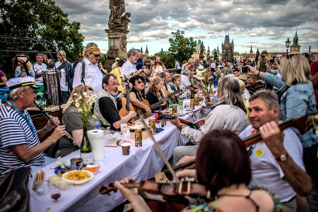 Musicians perform as diners sit at a gigantic table measuring 515 meters (1,690 feet) in length and spanning the entirety of the iconic Charles Bridge in Prague, Czech Republic, 30 June 2020. The massive dinner party came after an easing of the restrictions imposed in a bid to slow down the spread of the pandemic COVID-19 disease caused by the SARS-CoV-2 coronavirus. The event's organizers covered the colossal table with a white tablecloth and adorned it with flowers. Attendees were encouraged to bring their own food and share it with others. The still-low number of foreign visitors to the Czech Republic due to the coronavirus pandemic also provided an opportunity for locals to enjoy one of their city's most famous landmarks without the habitual hubbub from the throngs of tourists that usually crowd the picturesque capital. (Photo by Martin Divíšek/EPA/EFE)