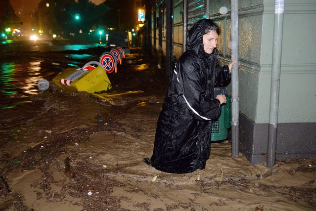 A woman walks through flood water during heavy downpour at a street in Genoa, Italy, 10 October 2014. At least one person died due to flooding after heavy rains caused the Bisagno river, which runs through Genoa city to overflow. Part of the city was in black-out with flooded streets and parked cars dragged away by the water's force. (Photo by Luca Zennaro/EPA)