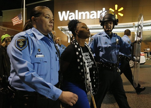 A protester is detained by police officers during a demonstration at a Walmart store in St. Louis, Missouri, October 13, 2014. Hundreds of people demonstrated in the pouring rain in the St. Louis area on Monday, staging a series of rolling protests in the latest show of anger over the police killing of an unarmed black teenager in August.  (Photo by Jim Young/Reuters)