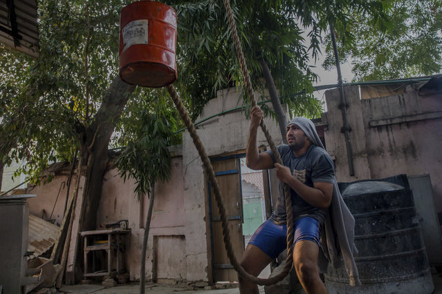 In this November 20, 2017 photo, an Indian Kushti wrestler warms up by pulling a rope that's threaded through a pulley and hauls into the air a bucket filled with concrete during his daily training at an akhada, a kind of wrestling hostel at Sabzi Mandi, in New Delhi, India. (Photo by Dar Yasin/AP Photo)
