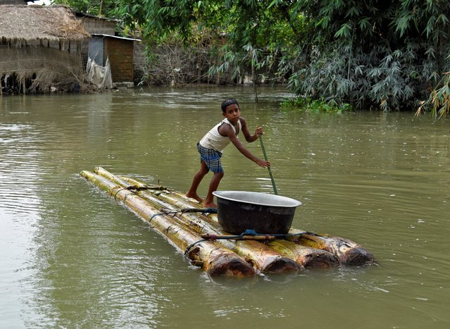 A boy transports a pot on a makeshift raft through a flooded area in Morigaon district, in Assam, July 20, 2020. (Photo by David Talukdar/Reuters)