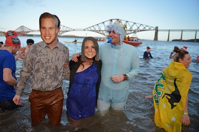 People wear Prince William, Duke of Cambridge and Catherine, Duchess of Cambridge masks as they joined over 1,000 New Year swimmers, many in costume, braved freezing conditions in the River Forth in front of the Forth Rail Bridge during the annual Loony Dook Swim on January 1, 2013 in South Queensferry, Scotland. Thousands of people gathered last night to see in the New Year at Hogmanay celebrations in towns and cities across Scotland.  (Photo by Jeff J. Mitchell)
