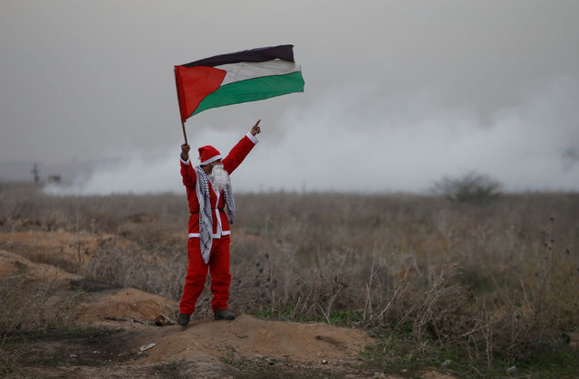 A demonstrator dressed as Santa Claus holds a Palestinian flag as Israeli troops fire tear gas during a protest against U.S. President Donald Trump's decision to recognize Jerusalem as the capital of Israel, near the border with Israel in the east of Gaza City December 19, 2017. (Photo by Mohammed Salem/Reuters)