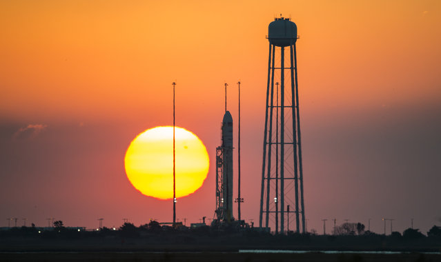 A handout photograph made available by NASA showing the Orbital Sciences Corporation Antares rocket, with the Cygnus spacecraft onboard, is seen on launch Pad-0A during sunrise, at NASA's Wallops Flight Facility in Virginia, October 26, 2014. The Antares will launch with the Cygnus spacecraft filled with over 5,000 pounds of supplies for the International Space Station, including science experiments, experiment hardware, spare parts, and crew provisions. (Photo by Joel Kowsky/EPA)