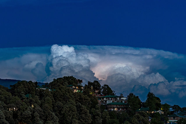 A flash of lightning lights up a raincloud hovering over a township in Dharmsala, India, Sunday, April 19, 2020. (Photo by Ashwini Bhatia/AP Photo)